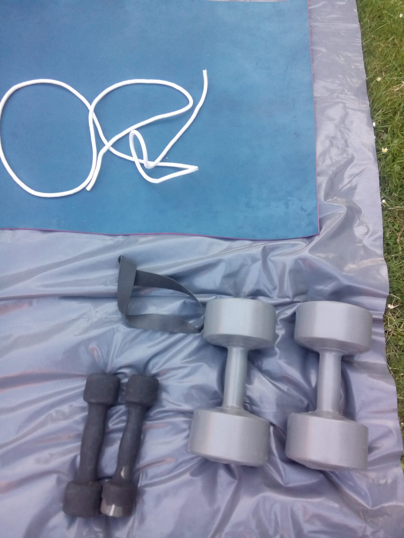 two sets of dumbells a skipping rope and a yoga mat